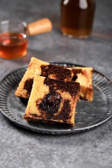 Tea time met plakje marmeren reiscake, vierkante cake met gesmolten chocolade in het midden. geserveerd op rustiek bord