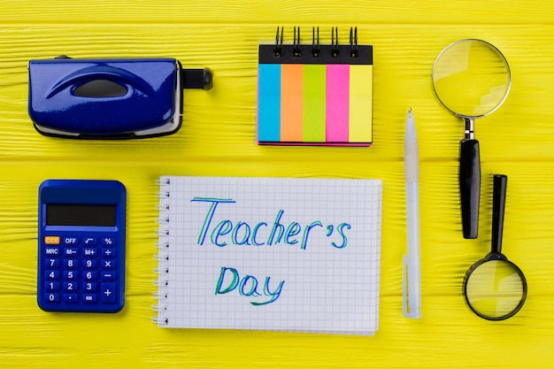 Teacher's day concept plat lag. briefpapier educatieve dingen op gele houten tafel.