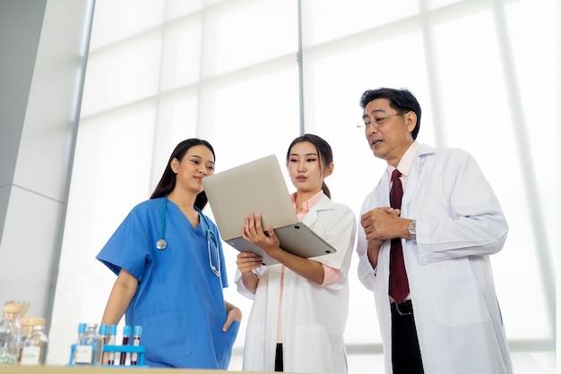 Team aziatische artsen die samen staan en een laptop-notebookcomputer gebruiken om te praten, bespreken