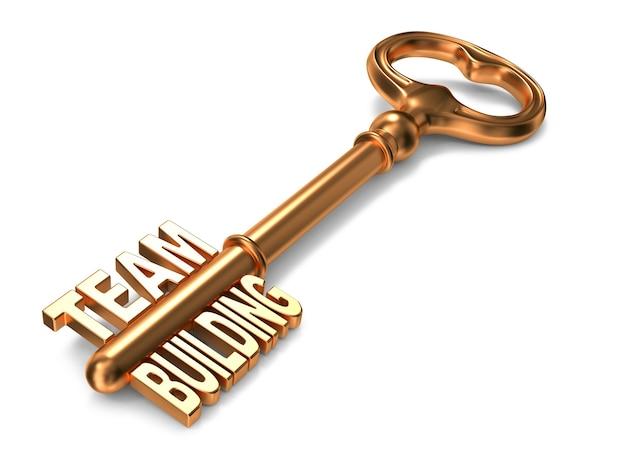 Team bulding-tekst op gouden sleutel op witte achtergrond