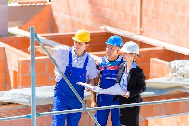 Team dat bouw of de bouwplaatsplannen bespreekt