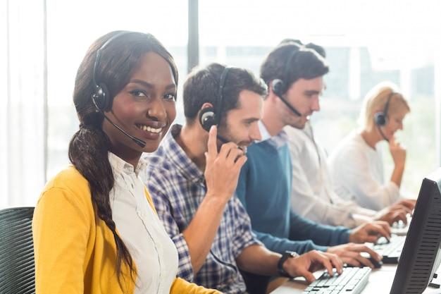 Team dat op computer met hoofdtelefoon werkt