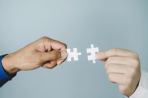 Team dat twee puzzelstukken probeert te verbinden