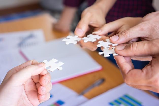 Team dat vier raadselspuzzel samen plaatst voor teamconcept