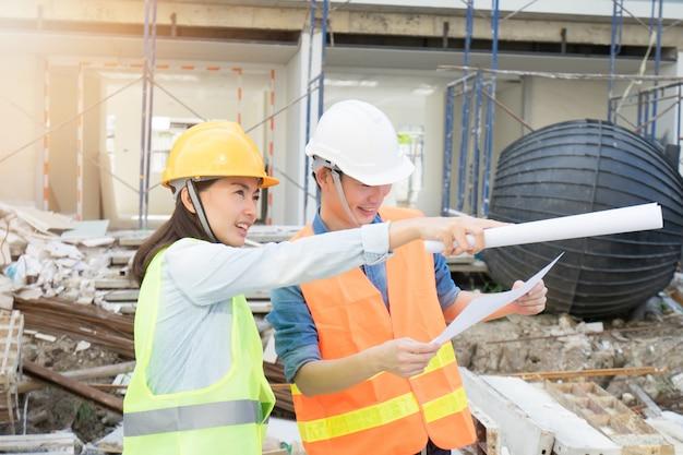 Team engineering die gele helm dragen en bij bouwwerf werken
