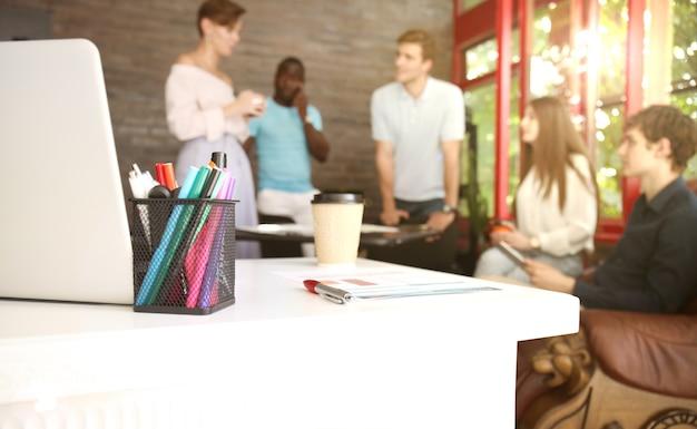 Team jonge professionals met een informele discussie op kantoor. leidinggevenden met vriendelijke discussie tijdens pauze.