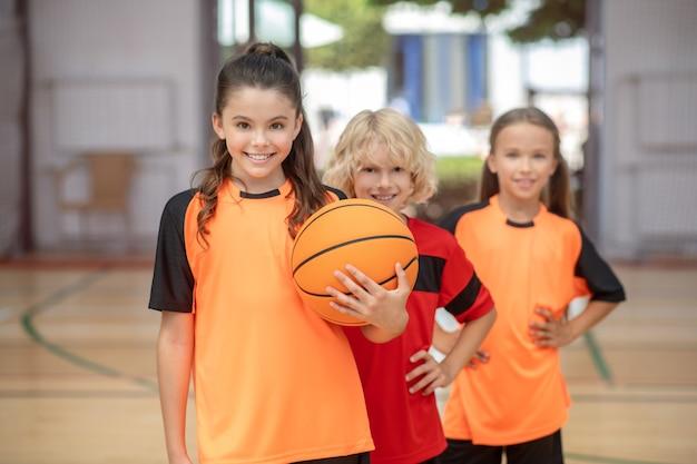 Team. kinderen in sportkleding staan met een bal en glimlachen