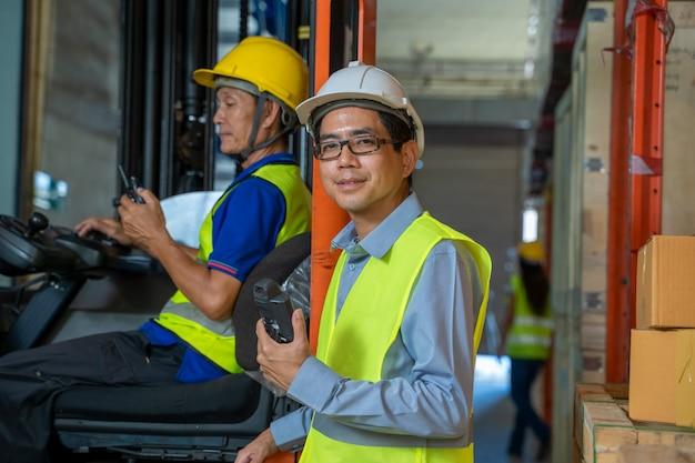 Team magazijnmedewerkers in magazijn met managers werken bij het grote magazijn, groothandel, logistiek, mensen en export concept.