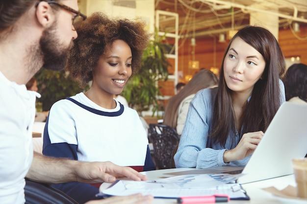 Team met bijeenkomst op coworking space, plannen en visie bespreken, nieuwe zakelijke oplossingen en strategie creëren met behulp van laptop.