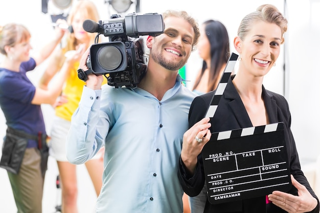 Team of cameraman met camera en vrouw met klap of bord op filmset
