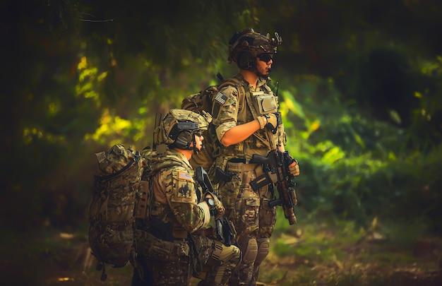 Team speciale krachten. soldaat aanvalsgeweer met geluiddemper. sluipschutter in het bos.