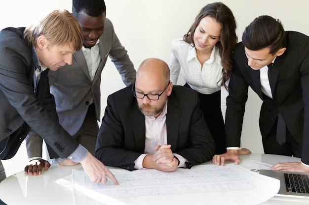 Team van architecten blauwdrukken bestuderen tijdens vergadering tijdens het werken aan een nieuw technisch project.