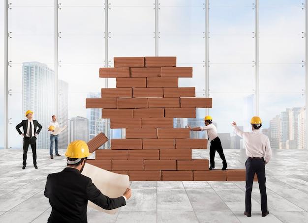 Team van architecten die aan een bakstenen bouwproject werken en analyseren