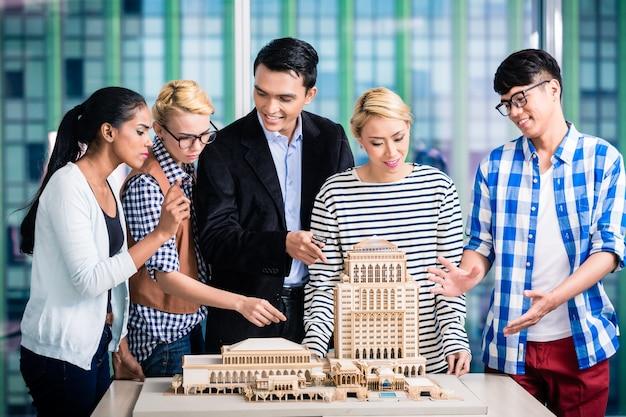 Team van architecten die modelbouw in presentatie aan klant presenteren