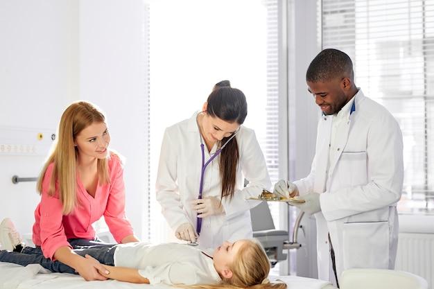 Team van artsen die samenwerken tijdens de behandeling van een kind meisje patiënt liggend op het ziekenhuisbed, afrikaanse man en blanke vrouw raadplegen meisje en houden medische check-up
