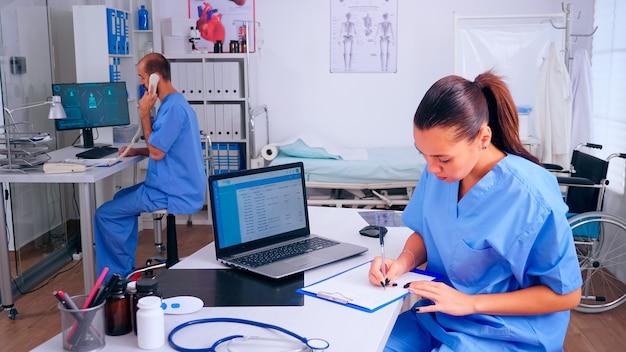 Team van artsen die werkzaam zijn in de ziekenhuiskliniek, verpleegster die aan de telefoon praat en assistent die aantekeningen maakt. arts in de geneeskunde uniforme schrijflijst van geraadpleegde, gediagnosticeerde patiënten, die onderzoek doen.