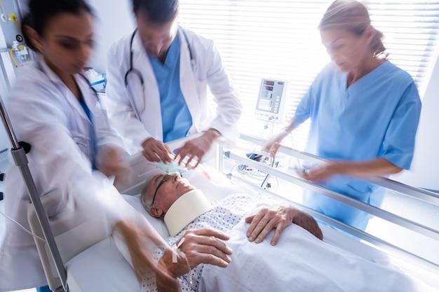 Team van artsen die zuurstofmasker op een mannelijk hoger geduldig gezicht zetten