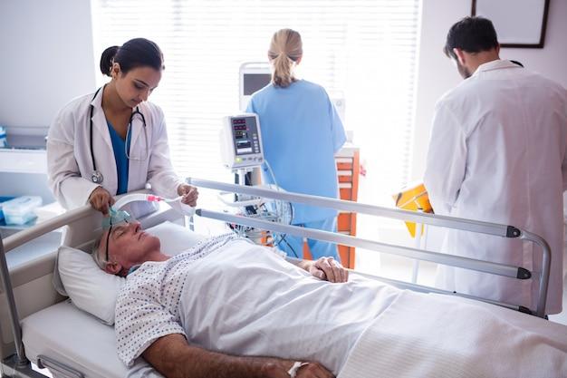 Team van artsen die zuurstofmasker op geduldig gezicht zetten