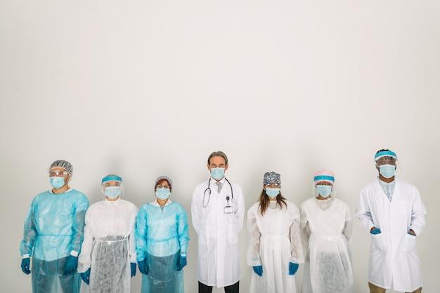 Team van artsen en verpleegsters die wegwerpbeschermingspakken en gezichtsmaskers dragen om covid19 te bestrijden