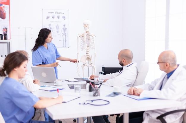 Team van artsen in het ziekenhuiskantoor die diagnose stellen in de vergaderruimte van het ziekenhuis. kliniek deskundige therapeut in gesprek met collega's over ziekte, medische professional.