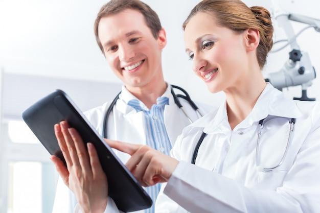 Team van artsen in kliniek met tabletcomputer