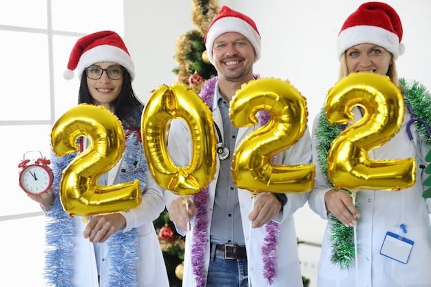Team van artsen in rode hoofdletters houdt het nummer tegen de achtergrond van nieuwjaarsboomgeneeskunde en