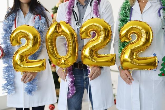 Team van artsen in witte jassen houden nummers nieuwjaar en kerstconcept