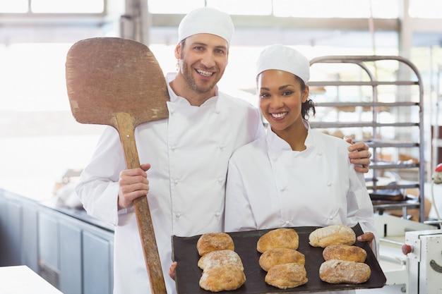 Team van bakkers die bij camera met dienbladen van broden glimlachen