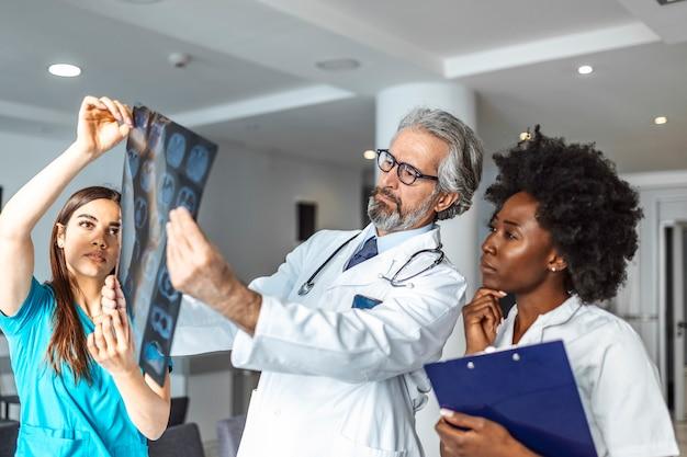 Team van beroepsbeoefenaren in de gezondheidszorg op zoek xray van de longen van de patiënt