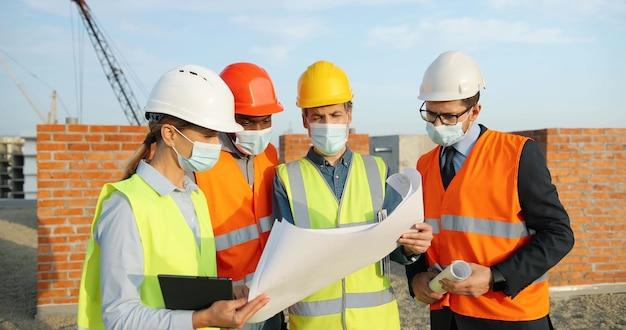 Team van bouwers van gemengde rassen, mannen en vrouwen in helmen en medische maskers, staan aan de bovenkant van het gebouw en bespreken het ontwerp van het bouwplan. coronavirus concept. ingenieurs en architecten.