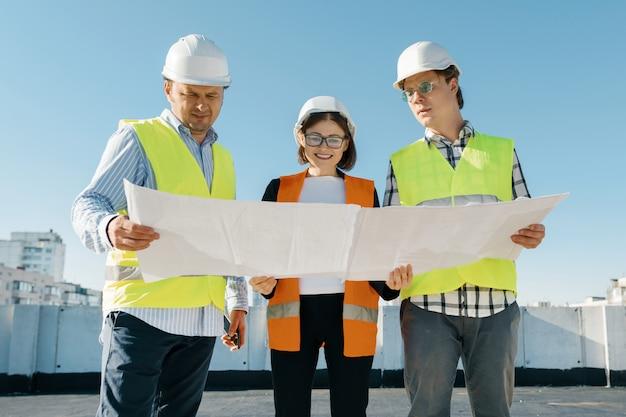 Team van bouwersingenieurs op een bouwplaats, die blauwdruk lezen
