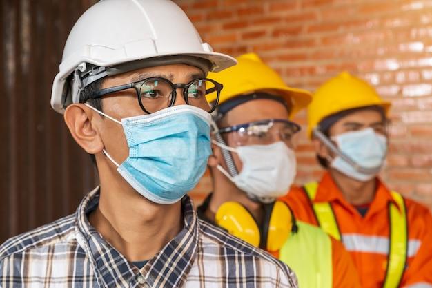 Team van bouwingenieurs en drie architecten staan klaar om medische maskers te dragen. corona of covid-19 dragen maskers tijdens het ontwerp van de constructie.