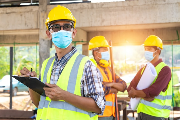 Team van bouwingenieurs en drie architecten staan klaar om medische maskers te dragen