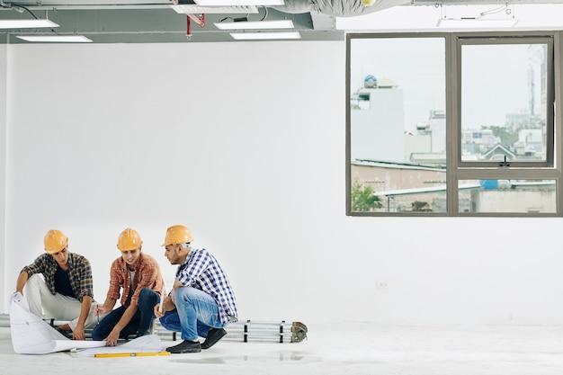 Team van bouwvakkers blauwdrukken van de vloer van lege ruimte in industrieel gebouw controleren