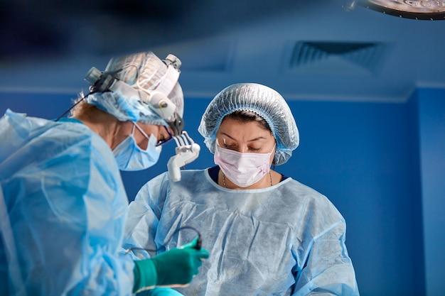Team van chirurgen maakt een invasieve operatie. portret van chirurgenclose-up. werk met een coagulerend instrument, vasculaire coagulatie