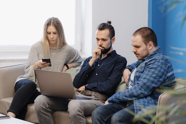 Team van drie mensen die werken op laptop op kantoor op de bank