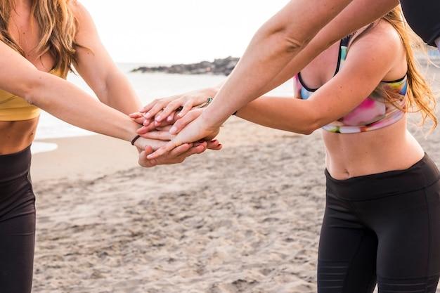 Team van drie mooie blanke vrouwenlichamen met handen in elkaar die zich voorbereiden op een intensieve training of het einde van de gymles vieren