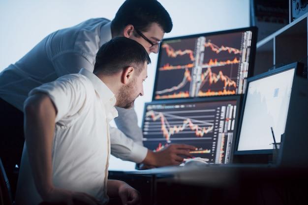 Team van effectenmakelaars voert een gesprek in een donker kantoor met schermen. gegevens, grafieken en rapporten analyseren voor investeringsdoeleinden. creatieve teamwork handelaren