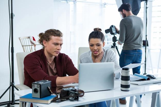 Team van fotografen die over laptop bij bureau werken