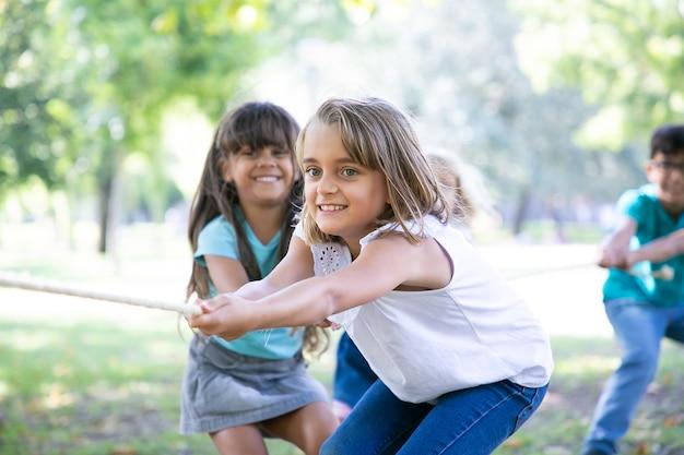 Team van gelukkige kinderen die touw trekken, touwtrekken spelen, genieten van buitenactiviteiten. groep kinderen plezier in park. jeugd of teamwerk concept