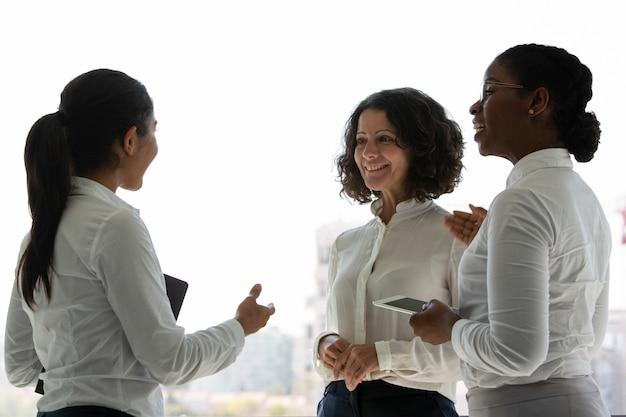 Team van gelukkige vrouwelijke collega's chatten