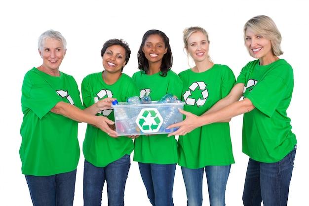 Team van gelukkige vrouwelijke milieuactivisten die doos van recyclables houden