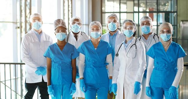 Team van gemengd ras team van professionele mannelijke en vrouwelijke artsen in het ziekenhuis. binnen. internationale groep medici in medische maskers. multi-etnische artsen in toga's en uniformen in de kliniek.