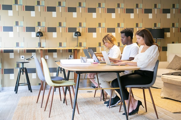 Team van gerichte ontwerpers zitten samen aan tafel met blauwdrukken en werken aan een project