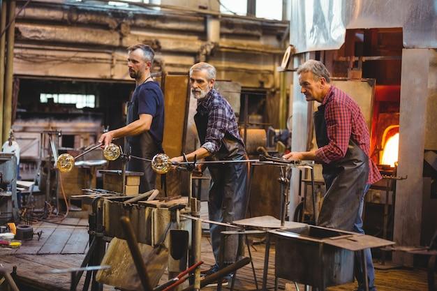 Team van glasblazers die een glas op de blaaspijp vormen