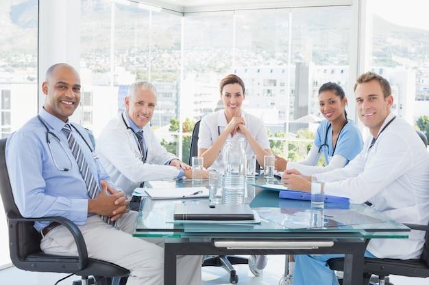 Team van glimlachende artsen die een vergadering in de vergaderzaal hebben