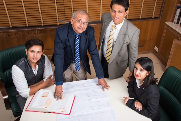 Team van indiase architecten of bouwers die een huisvestingsproject opstellen of bespreken met het bouwmodel en plannen rond de selectieve focus van de vergadertafel