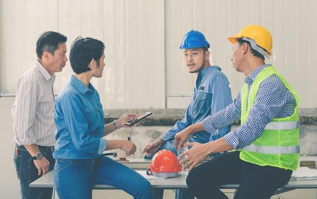 Team van ingenieur en architecten die het werk bouwen bij worksite bespreken