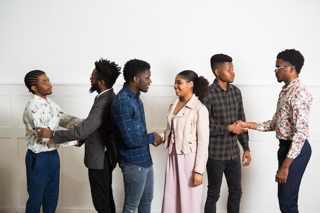 Team van jonge afrikaanse mensen binnenshuis handen schudden