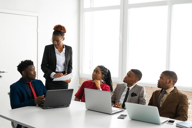 Team van jonge afrikaanse mensen op kantoor aan tafel met een laptop